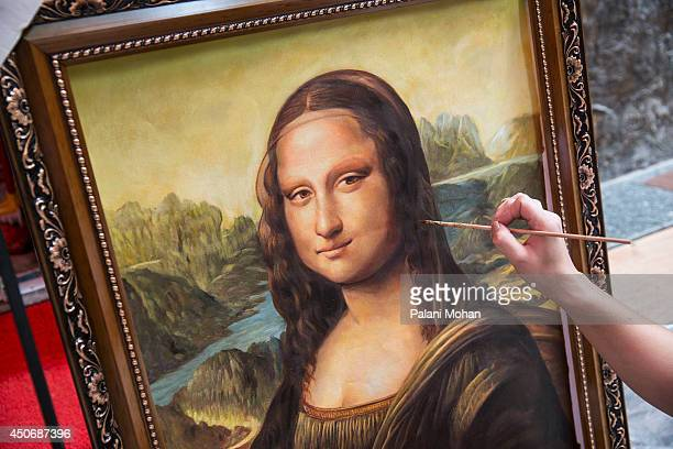A artist works on a replica of the famous Mona Lisa outside a gallery at the artist village on June 11 2014 in Shenzhen China The Dafen Artist...
