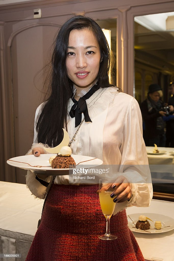 Artist Yi Zhou poses with a cake and a cocktail she has designed for Hotel Lutetia during the 'Rendez Vous Chez Yi' cocktail inauguration at Hotel Lutetia on November 14, 2013 in Paris, France.