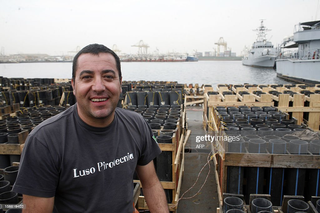 Artistic director Joao Paulo Ribeiro, working for a Portuguese pyrotechnic company, smiles next to fireworks waiting to be moved offshore and to be lit on New Year's Eve, on December 30, 2012 in the port of Dakar. Senegal's capital will organize the 'biggest fireworks' of its history and plans on using six tons of pyrotechnical material, operated by Portuguese pyrotechnists. AFP PHOTO / MAMADOU TOURE BEHAN