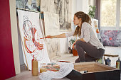 Artistic girl sitting in studio and paint on easel while sitting on chair. In hand paint brush.