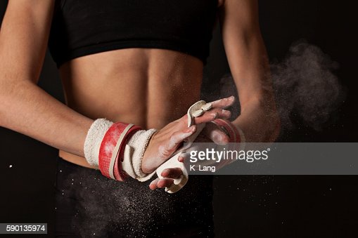Artistic Gymnast Chalking up Grips for Uneven Bars : Stock Photo