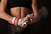 Close up of female gymnasts hands grips and cloud of chalk