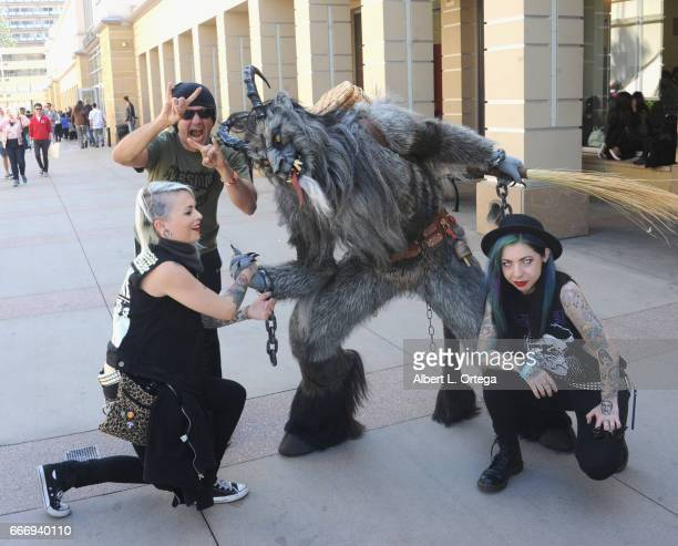 Artist/musician Neil D'Monte MJ Destiny pose with Krampus on day 2 of the 2017 Monsterpalooza held at Pasadena Convention Center on April 9 2017 in...