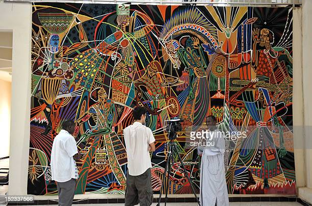 Artists and journalists stand in front of a handwoven tapestry which will decorate the headquarters of the United Nations in New York on September 4...