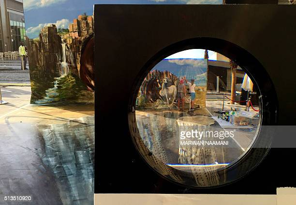 Artists are seen through a magnifier as they work on a 3D canvas on March 3 2016 near the Jumeirah Beach Residence in Dubai during the Canvas...
