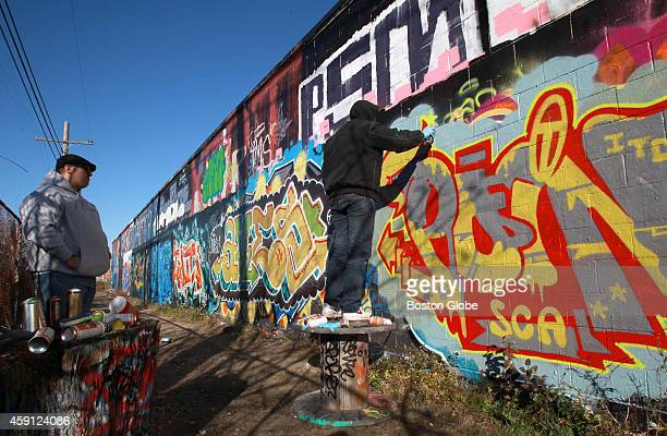 Artists at work on the Beverly Wall a legal graffiti wall alongside the commuter rail tracks in downtown Beverly Mass on November 15 2014 The wall is...