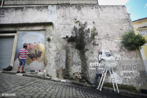 Artists Carlos Bobi and Caze paint graffiti in the Providencia ÔfavelaÕ community the oldest favela in Rio as part of the ÔProvidencia GalleryÕ...