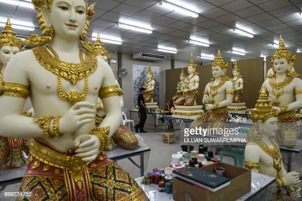 Artists chat whilst having a break from painting statues in a warehouse next to the funeral pyre and surrounding pavilions for the late Thai King...