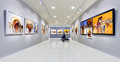 In a art gallery young woman visits an art exhibition and watches artist's collection.