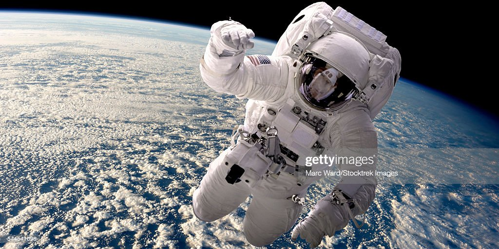 Artists concept of an astronaut floating in outer space. A cloud covered Earth is below.