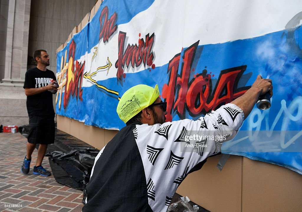 Artists Daniel Castillo, right, and Delton Demarest, spray paint on a large canvas mural propped up on a cardboard box wall at Civic Center Park July 01, 2016. ProgressNow Colorado hosted a peaceful event titled, Tearing Down the Wall of Hate in conjunction with GOP Presidential candidate Donald Trump's visit to the Western Conservative Summit.