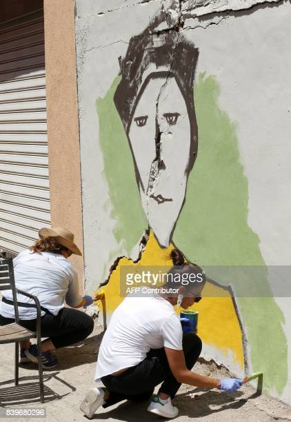 Artists draw a mural on a wall as part of the 'Ouzville' project in Beirut's southern Ouzai neighbourhood on August 19 2017 Starting 18 months ago...