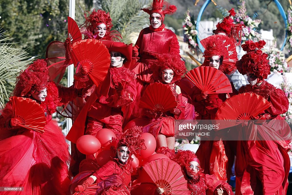 Artists dressed in red and holding fans parade on February 13, 2016 in coastal city of Nice, southeastern France during the 132nd Nice Carnival. The carnival strats February 13 until 28 February 2016, and this year's theme celebrates the 'King of Medias'. / AFP / VALERY HACHE