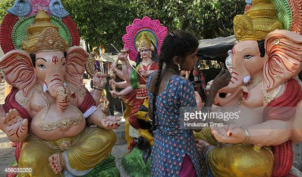 Artists giving finishing touched to idols of Hindu deities ahead of Navratri celebrations on September 24 2014 in Noida India The word Navaratri...