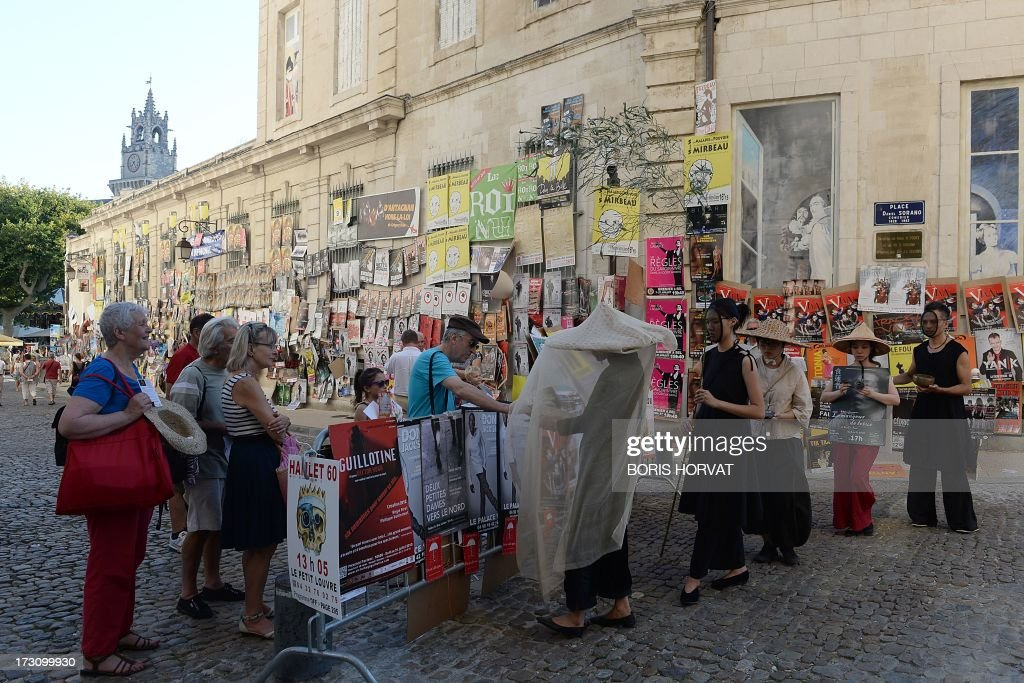 Artists hand out pamphletes of various theater shows on July 6, 2013 next to Palais des Papes in Avignon, southeastern France, during the 67th International Theatre festival.
