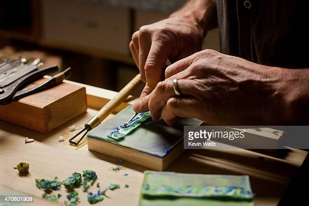 Artist's hands working on art piece with tools