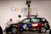 Artists paint a German Google Street View car at the Google stand at the CeBIT Technology Fair on March 2 2010 in Hannover Germany Google's Street...