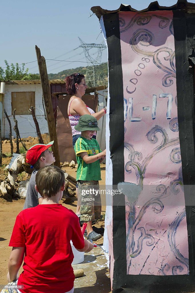 Artists paint a shack at the Alaska Informal settlement on March 24, 2013 in Mamelodi, South Africa. The Viva Foundation hosted the second Mams Art Festival at the informal settlement over the weekend. The art festival focuses on creating the world's first living art gallery by transforming shacks into art work.