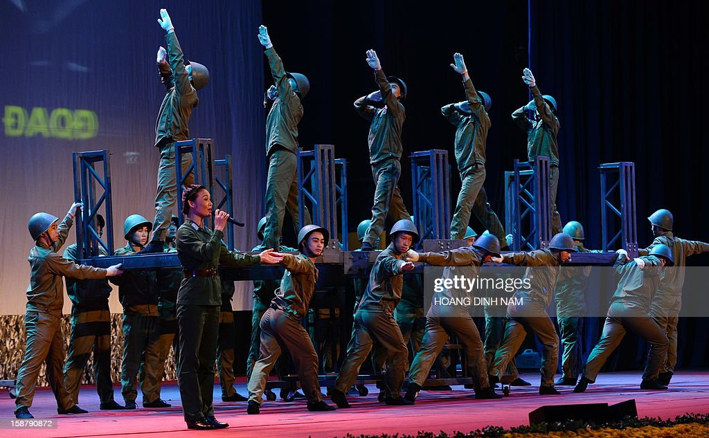 Artists perform at the venue marking the 40th anniversary of 'Dien Bien Phu in the air' or victory over US Airforce B-52's Christmas bombing, in Hanoi on December 29, 2012. Hanoi claimed downing some 34 US B-52 aircrafts during the 12-day US bombing campaign in December 1972 over Hanoi and neighbouring provinces. The meeting is the final event of a month-long celebration organised by the government. AFP PHOTO/HOANG DINH Nam