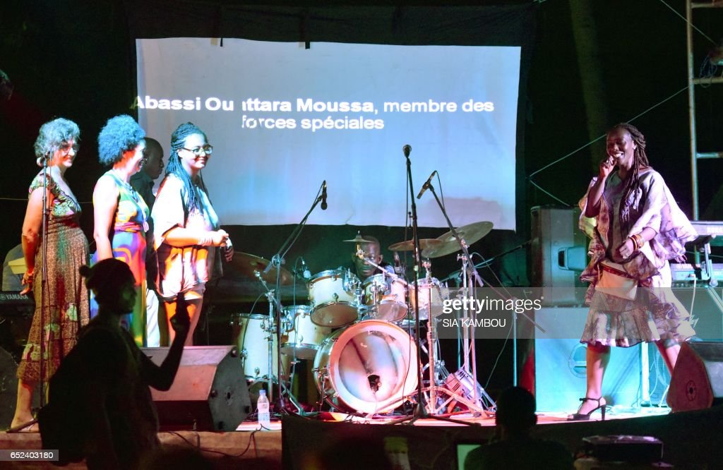 Artists perform on a stage, while the name of a victim is displayed on a screen, during an hommage to the victims of March 13, 2016 terror attack at the resort of Grand Bassam, east of Abidjan, on March 11, 2017. The attack that killed 19 people, the first of its kind in the Ivory Coast, was claimed by Al-Qaeda in the Islamic Maghreb, which has also carried out assaults on tourist hotspots in Mali and Burkina Faso. / AFP PHOTO / Sia KAMBOU