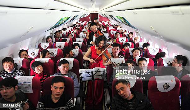 Artists play violins for passengers on a passenger flight on January 31 2016 in Kunming Yunnan Province of China Artists held a spring concert for...