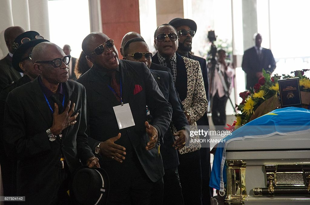 Artists sing over the coffin of rumba musician Papa Wemba during his funeral in Kinshasa on May 2, 2016. Democratic Republic of Congo's rumba king Papa Wemba was posthumously awarded one of his country's highest honours, a week after he collapsed on stage and died aged 66. / AFP / JUNIOR