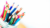 Artist's supplies: Watercolor pencils in glass jar on desk