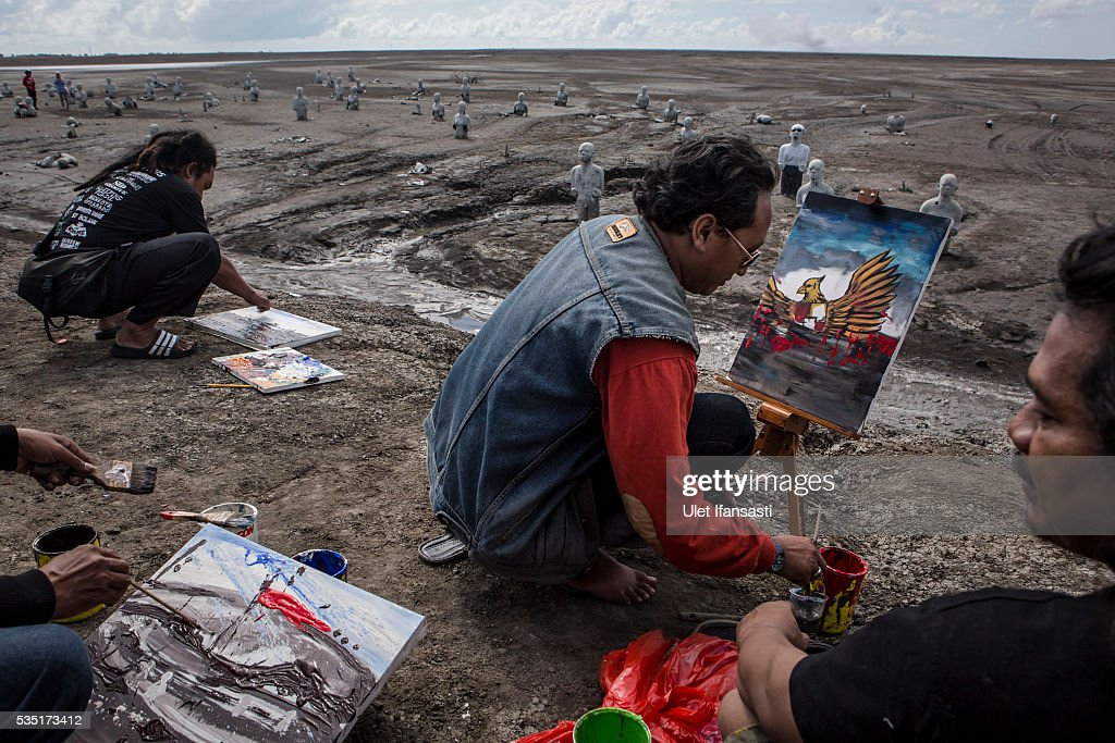 Artists take action to paint together at mudflow during the tenth anniversary of the mudflow eruption on May 29, 2016 in Sidoarjo, East Java, Indonesia. Residents of villages which were damaged by the Sidoarjo mudflow have finally received compensation from the Indonesian oil and gas company, PT Lapindo Brantas, after almost ten years. The mudflow eruption is suspected to have been triggered by the drilling activities of the oil and gas company, though they refute the claims, instead blaming a 6.3 magnitude earthquake which struck the neighbouring city of Yogyakarta, a city 150 miles west of a drill site in Sidoarjo, two days before the mudflow eruption on May 27th, 2006. According to reports, twenty lives were lost and nearly 40,000 people displaced, with damages topping USD 2.7 billion. Ten years on since the eruption the mud geysers still continue to spurt mud out on a daily basis and high levels of heavy metals have been detected in nearby rivers.