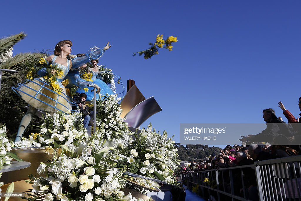 Artists throw flowers to onlookers as they stand on floats during the parade on February 13, 2016 in the coastal city of Nice, southeastern France, during the 132nd Nice Carnival. The carnival starts February 13 until 28 February 2016, and this year's theme celebrates the 'King of Medias'. / AFP / VALERY HACHE