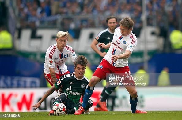 Artjoms Rudnevs and Lewis Holtby of Hamburg challenge Roman Neustaedter of Schalke during the Bundeslga match between Hamburger SV and FC Schalke 04...