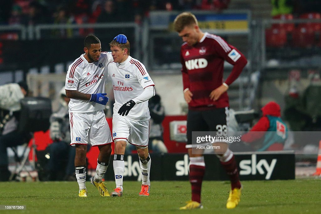 Artjoms Rudnevs (back R) of Hamburg celebrates his team's first goal with team mate Dennis Aogo as Alexander Esswein of Nuernberg reacts during the Bundesliga match between 1. FC Nuernberg and Hamburger SV at Easy Credit Stadium on January 20, 2013 in Nuremberg, Germany.