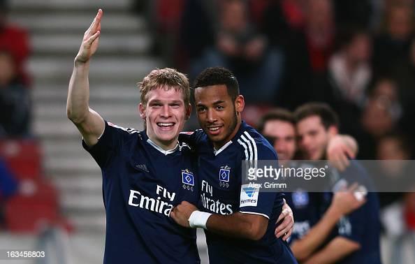 Artjoms Rudnevs of Hamburg celebrates his team's third goal with team mate Dennis Aogo during the Bundesliga match between VfB Stuttgart and...