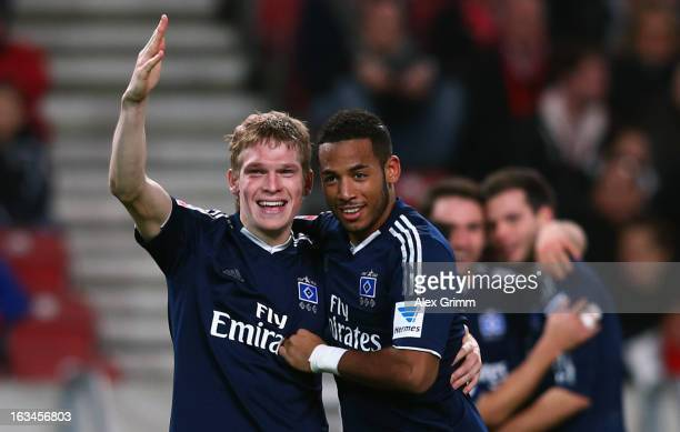 Artjoms Rudnevs of Hamburg celebrates his team's third goal with team mate Dennis Aogo during the Bundesliga match between VfB Stuttgart and...