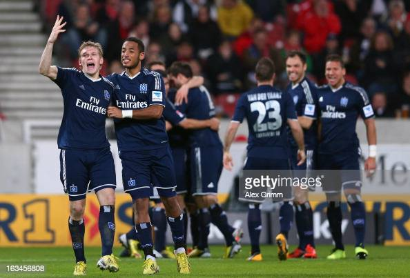 Artjoms Rudnevs of Hamburg celebrates his team's third goal with team mate Dennis Aogo and others during the Bundesliga match between VfB Stuttgart...