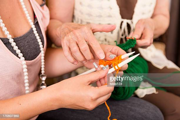 Arts Crafts: Sneior Woman shows Young Adult how to knit