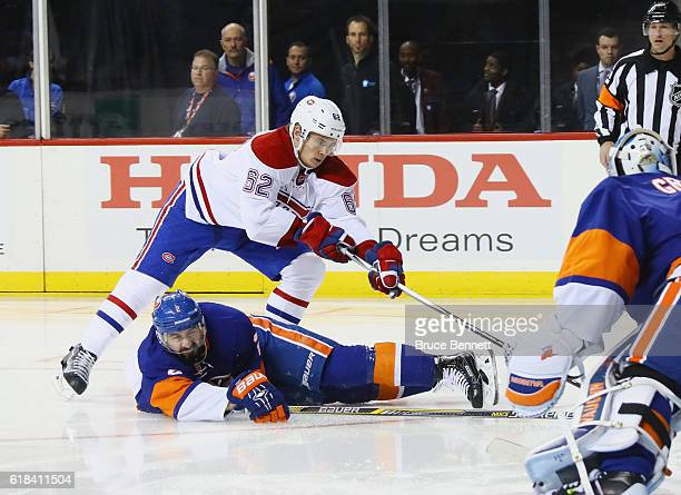 Artturi Lehkonen of the Montreal Canadiens moves the puck around Nick Leddy of the New York Islanders during the first period at the Barclays Center...