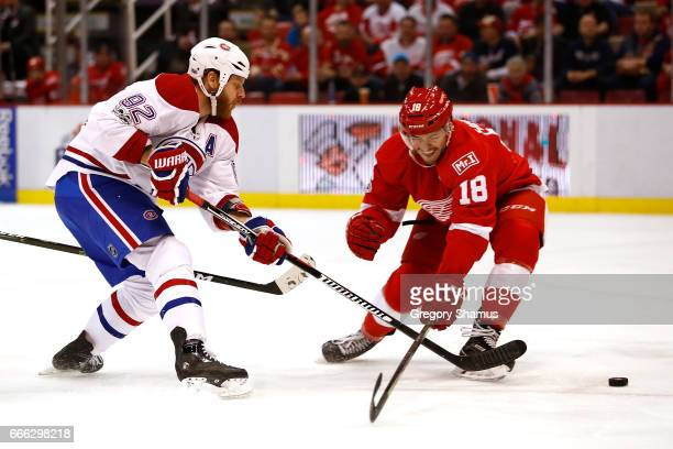 Artturi Lehkonen of the Montreal Canadiens takes a first period shot past the stick of Robbie Russo of the Detroit Red Wings at Joe Louis Arena on...