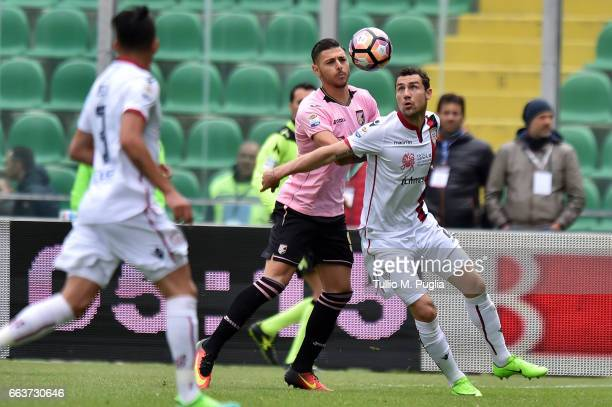 Artur Ionita of Cagliari is challenged by Giuseppe Pezzella of Palermo during the Serie A match between US Citta di Palermo and Cagliari Calcio at...