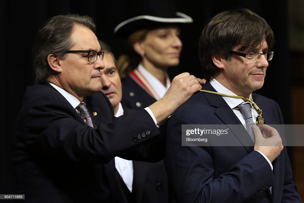 Artur Mas, former Catalan president, left, ties medal of the Catalan Presidency around Carles Puigdemont, Catalonia's incoming president, as he is sworn into office at the Palau de la Generalitat in Barcelona, Spain, on Tuesday, Jan. 12, 2016. The former mayor of Girona, a city near Spain's border with France, emerged as a last-minute compromise candidate as the fighting between two factions within the independence movement threatened to force new elections, jeopardizing their majority in the regional assembly. Photographer: Pau Barrena/Bloomberg via Getty Images
