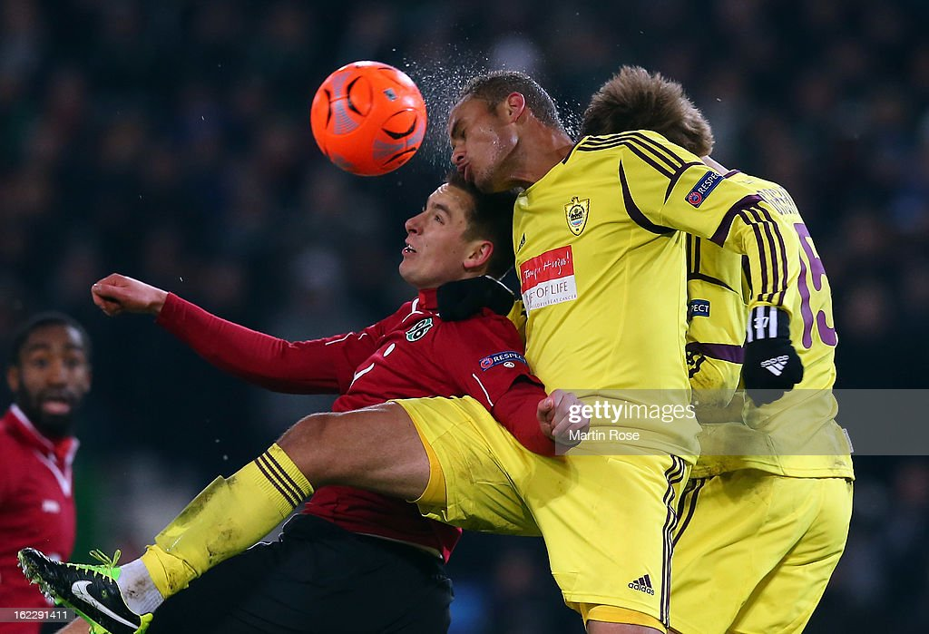 Artur Sobiech (L) of Hannover and Joao Carlos (R) of Makhachkala head for the ball during the UEFA Europa League Round of 32 second leg match between Hannover 96 and Anji Makhachkala at AWD Arena on February 21, 2013 in Hannover, Germany.