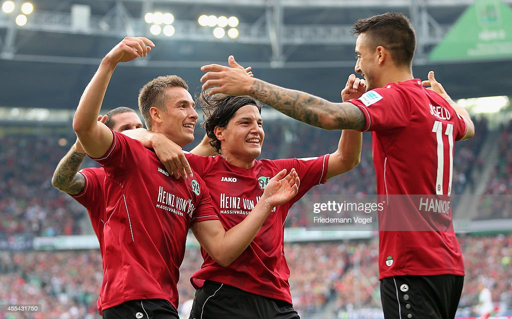 Artur Sobiech of Hannover celebrates scoring the second goal with Miiko Albornoz and Joselu during the Bundesliga match between Hannover 96 and...