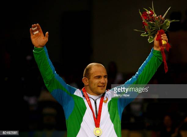 Artur Taymazov of Uzbekistan waves to the crowd after winning the gold medal in the men's 120 kg wrestling gold medal match held at the China...