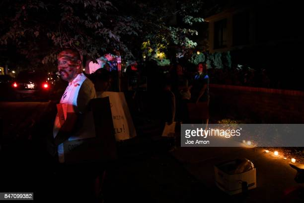 Arturo Hernandez Garcia looks on at police cars arriving as Ingrid Encalada Latorre and supporters hold a candle light vigil in front of the...