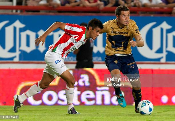 Arturo Javier Ledezma of Necaxa struggles for the ball with Dante Lopez of Pumas during a match as part of the Clausura Tournament 2011 at Victoria...