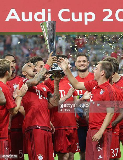 Arturo Vidal and Philipp Lahm of Bayern Muenchen hold the Audi Cup trophy celebrating their victory of the final match between FC Bayern Muenchen and...