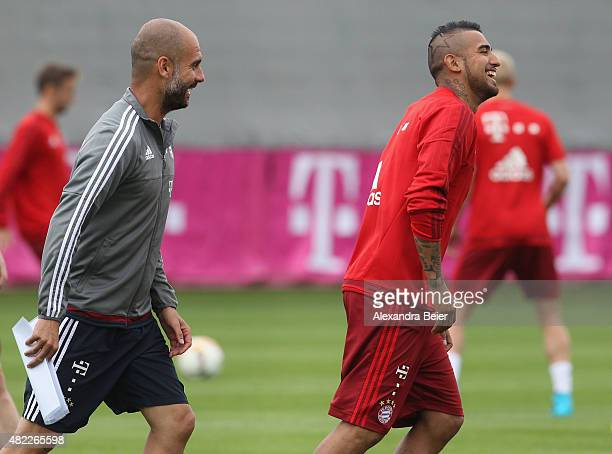 Arturo Vidal and team coach Josep Guardiola joke during the FC Bayern Muenchen training session at Bayern's training ground Saebener Strasse on July...