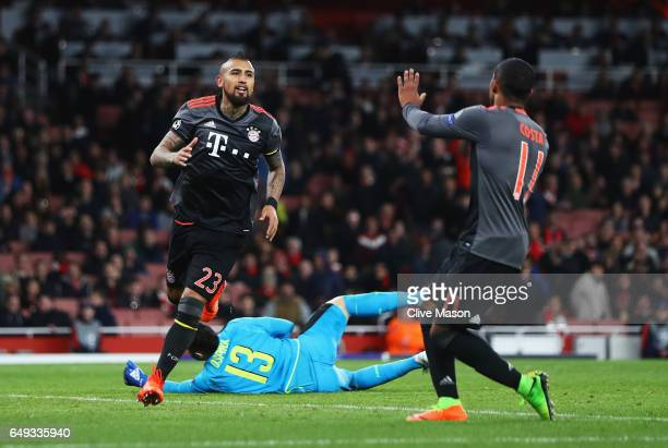 Arturo Vidal of Bayern Muenchen celebrates as he scores their fifth goal with Douglas Costa as David Ospina of Arsenal looks dejected during the UEFA...
