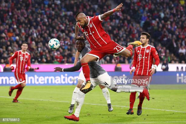 Arturo Vidal of Bayern Muenchen goes for a header against Daniel Opare of Augsburg during the Bundesliga match between FC Bayern Muenchen and FC...