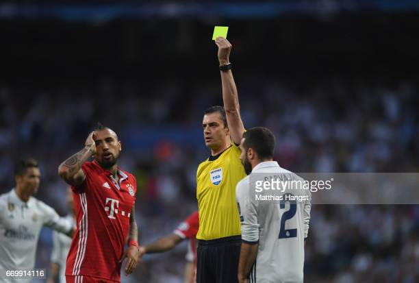 Arturo Vidal of Bayern Muenchen is shown a yellow card by referee Viktor Kassai during the UEFA Champions League Quarter Final second leg match...