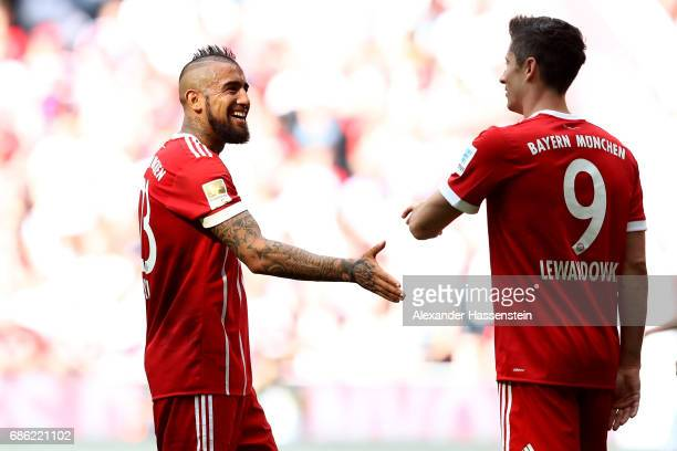 Arturo Vidal of Bayern Muenchen reacts with his team mate Robert Lewandowski during the Bundesliga match between Bayern Muenchen and SC Freiburg at...